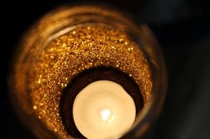 Lit candle inside the glittered jar